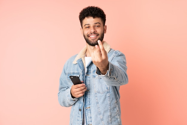 Młody człowiek maroka za pomocą telefonu komórkowego na białym tle na różowym tle robi nadchodzący gest