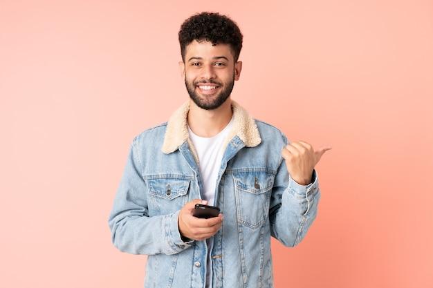 Młody człowiek maroka za pomocą telefonu komórkowego na białym tle na różowym tle, wskazując na bok, aby przedstawić produkt