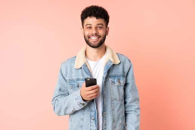 Młody człowiek maroka za pomocą telefonu komórkowego na białym tle na różowym tle z zaskoczenia wyrazem twarzy