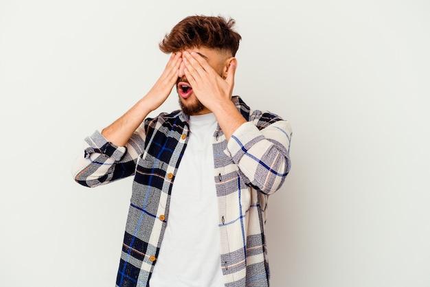 Młody człowiek marokański boi się zakrywających oczy rękami.