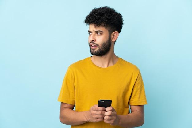 Młody człowiek marokański na białym tle na niebieskiej ścianie przy użyciu telefonu komórkowego i patrząc w górę