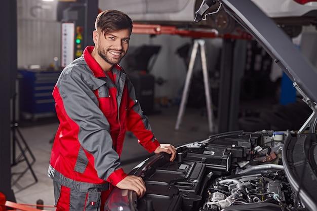 Młody człowiek mechanik pracuje na silniku samochodu