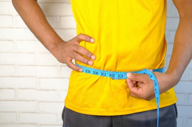 Młody człowiek mierzy jego talię z centymetrem z bliska
