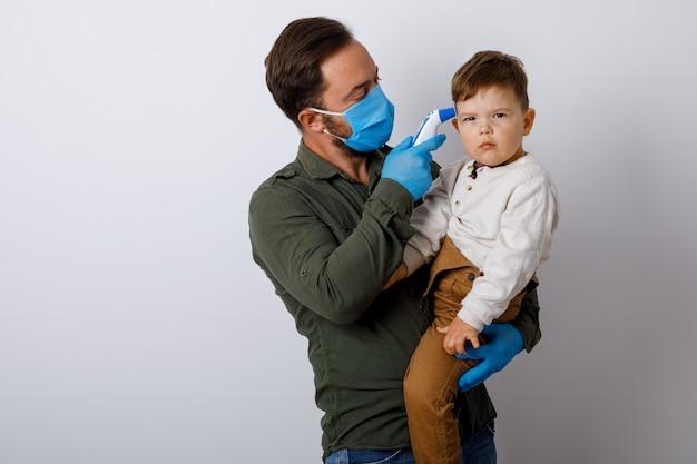 Młody człowiek mierzy temperaturę ciała małego chłopca