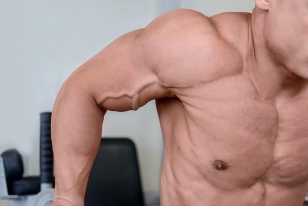 Młody człowiek mięśni, poćwiczyć w siłowni