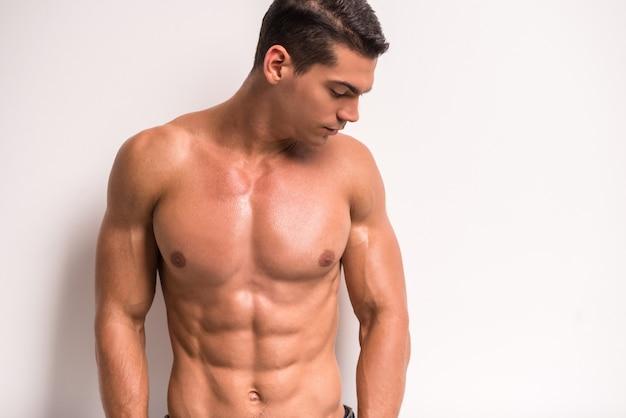Młody człowiek mięśni stoi