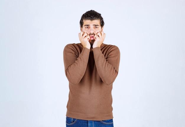 Młody człowiek model stojący i trzymający się za ręce w pobliżu twarzy.