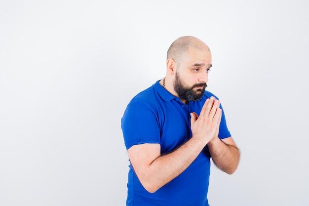 Młody człowiek modli się o coś w niebieskiej koszuli widok z przodu.