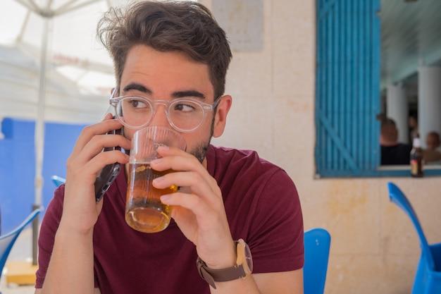 Młody człowiek mówi do telefonu komórkowego w restauracji