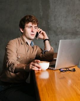 Młody człowiek mówi przez telefon w biurze