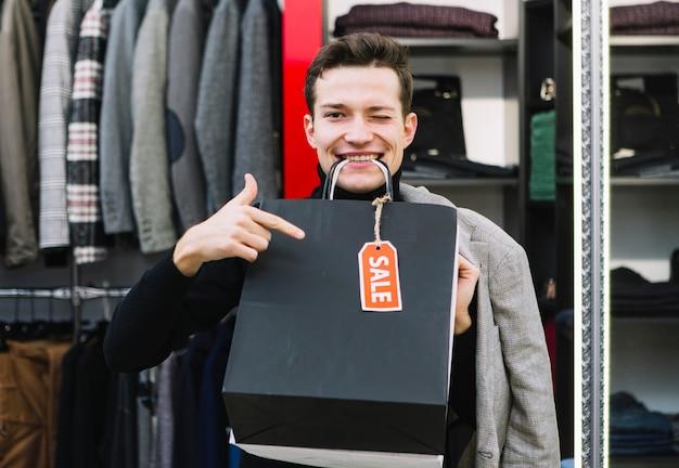 Młody człowiek mrugając oczami trzymając torby na zakupy w ustach