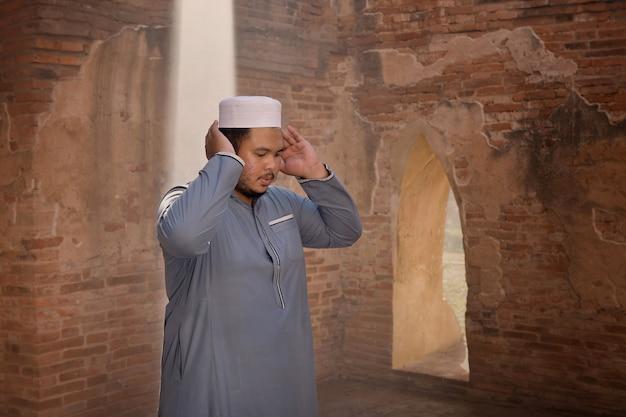Młody człowiek muzułmański modlący się w starym meczecie w ayutthaya, tajlandia