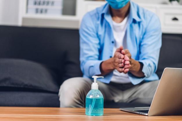 Młody człowiek mycie rąk żelem alkoholowym w kwarantannie dla koronawirusa w masce ochronnej z dystansem społecznym i przy użyciu komputera przenośnego pracującego w domu. praca z domu i koncepcja covid19
