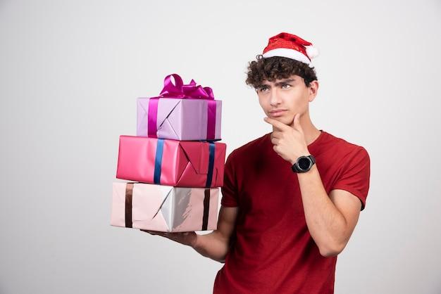 Młody człowiek myśli o czymś z pudełkami na prezenty.