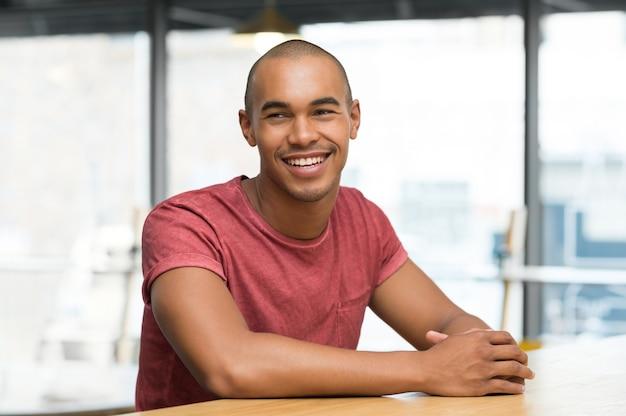 Młody człowiek myśli siedząc na krześle w kawiarni