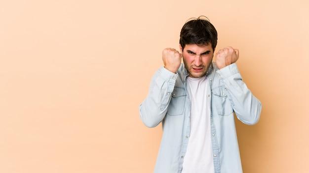 Młody człowiek na beżowej ścianie pokazuje pięść z agresywnym wyrazem twarzy.