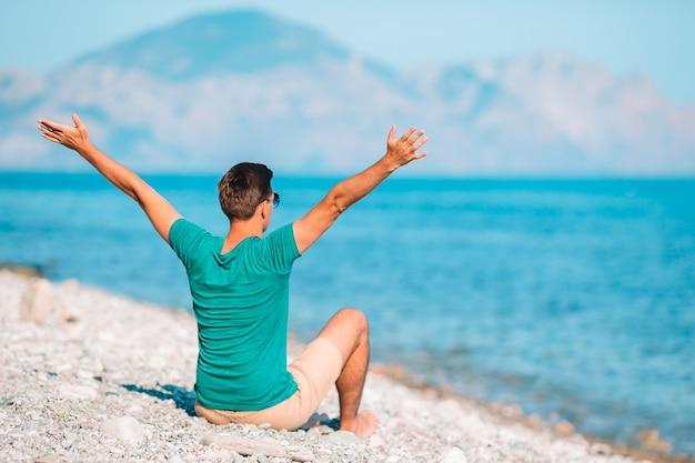 Młody człowiek na białej plaży na wakacjach