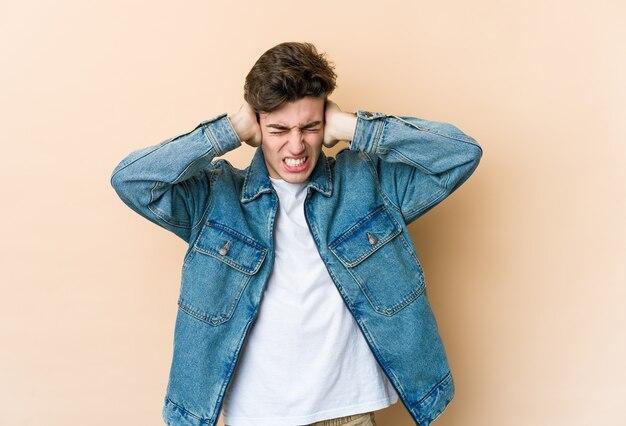 Młody człowiek na białym tle na beżowej ścianie obejmujące uszy rękami, starając się nie słyszeć zbyt głośnego dźwięku