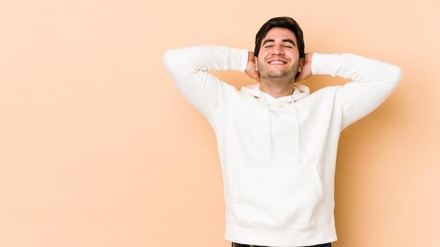 Młody człowiek na białym tle na beżowym tle, czując się pewnie, z rękami za głową.