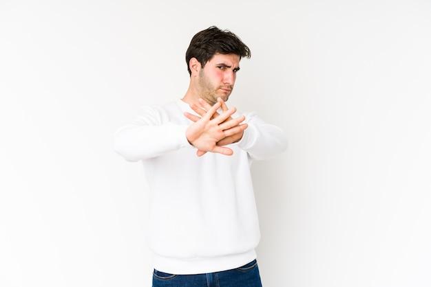 Młody człowiek na białym tle na białej przestrzeni robi gest odmowy