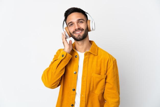 Młody człowiek na białym tle na białej ścianie słuchania muzyki