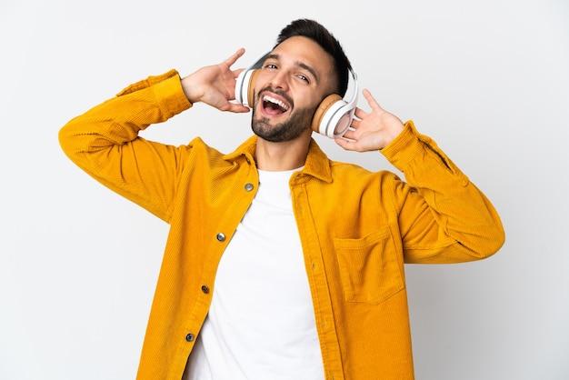 Młody człowiek na białym tle na białej ścianie, słuchanie muzyki