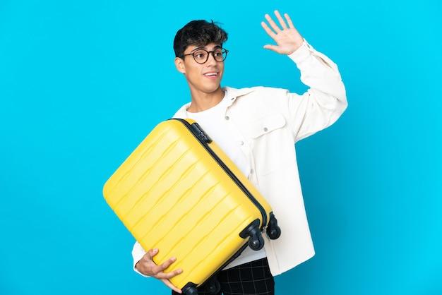 Młody człowiek na białym tle niebieski na wakacjach z walizką podróżną i pozdrawiając