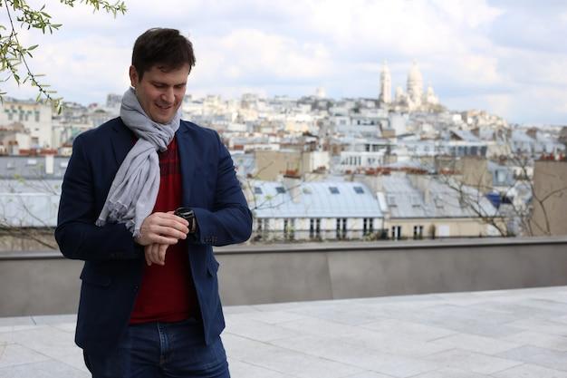 Młody człowiek na dachu w paryżu zegarek na zegarek na rękę w pobliżu bazyliki najświętszego serca