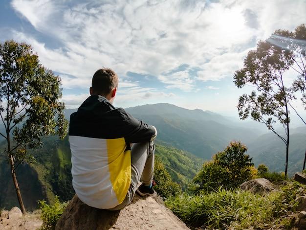 Młody człowiek na górze siedzi na kamieniu w pobliżu ella, sri lanka