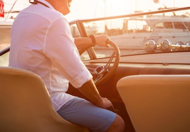 Młody człowiek na jachcie żaglowym. kierownicę trzymaj za ręce
