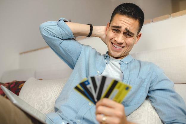 Młody człowiek na kanapie w domu z tabletem robi zakupy online.