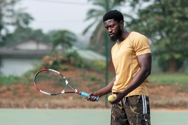 Młody człowiek na korcie tenisowym, grając