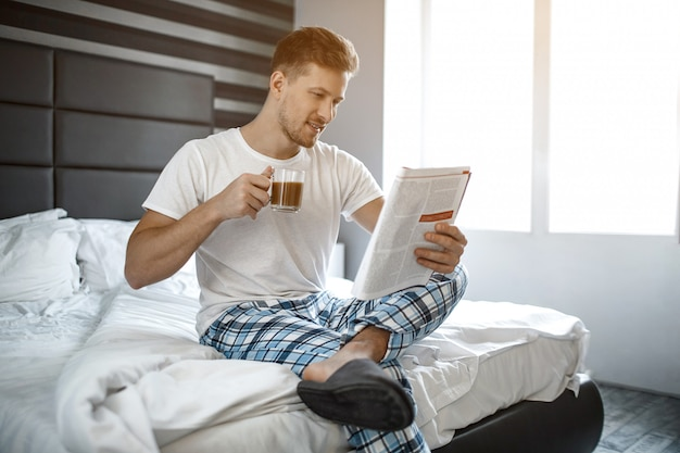 Młody człowiek na łóżku w nocy. siedzi i czyta dziennik guy z filiżanką kawy. miło i wesoło.