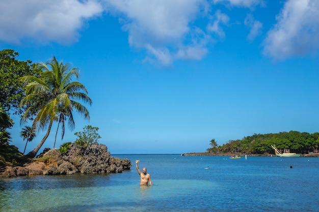 Młody człowiek na morzu karaibskim na west end beach na wyspie roatan. honduras