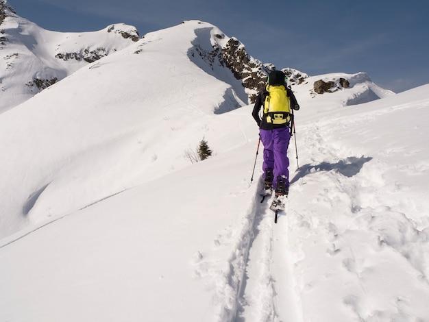 Młody człowiek na nartach na splitboard w górach