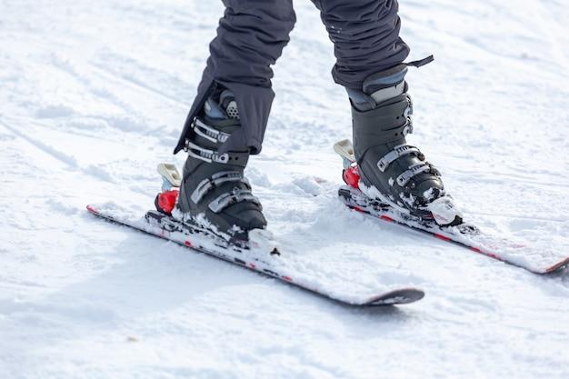 Młody człowiek na nartach ze stoków, sprzęt i ekstremalne sporty zimowe w miejscu na narty