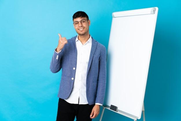 Młody człowiek na niebieskim tle, dając prezentację na tablicy i kciuki do góry