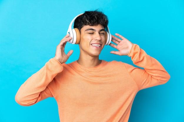 Młody człowiek na niebiesko słuchanie muzyki i śpiewu