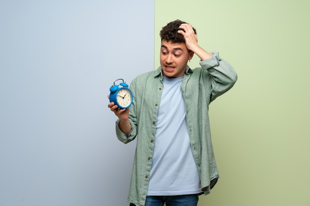 Młody człowiek na niebiesko-zieloną ścianę niespokojny, ponieważ się spóźnił i trzyma vintage budzik