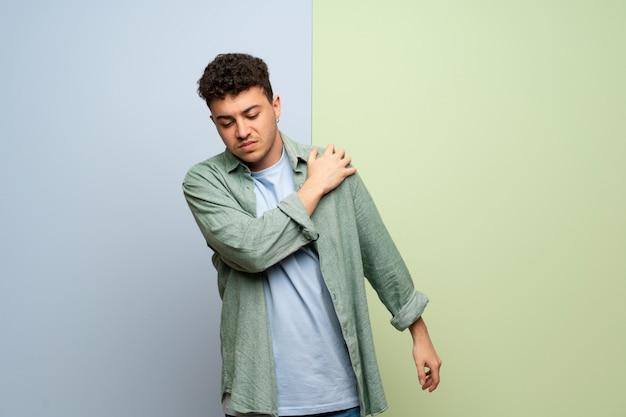 Młody człowiek na niebiesko-zielonej ścianie cierpiący z powodu bólu w ramieniu za to, że podjął wysiłek