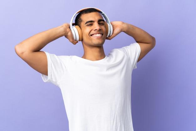 Młody człowiek na pojedyncze fioletowe ściany słuchania muzyki