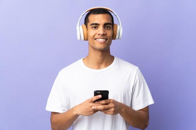 Młody człowiek na pojedyncze fioletowe ściany słuchanie muzyki z telefonu komórkowego i patrząc z przodu