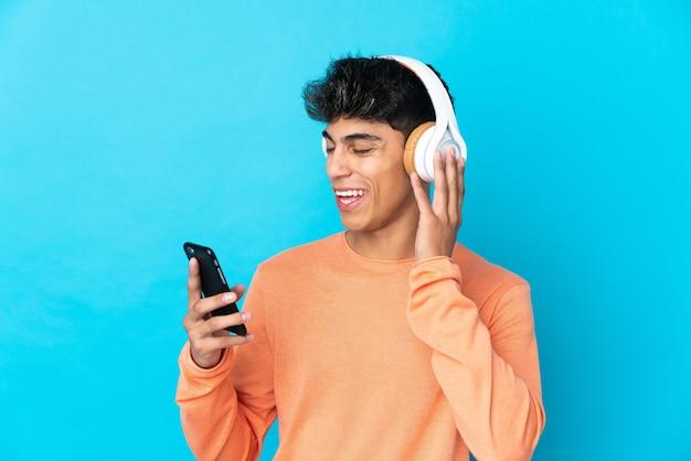 Młody człowiek na pojedyncze niebieskie słuchanie muzyki z telefonem komórkowym i śpiewem