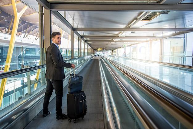 Młody człowiek na przejściu na lotnisku niosąc swój bagaż z uśmiechem