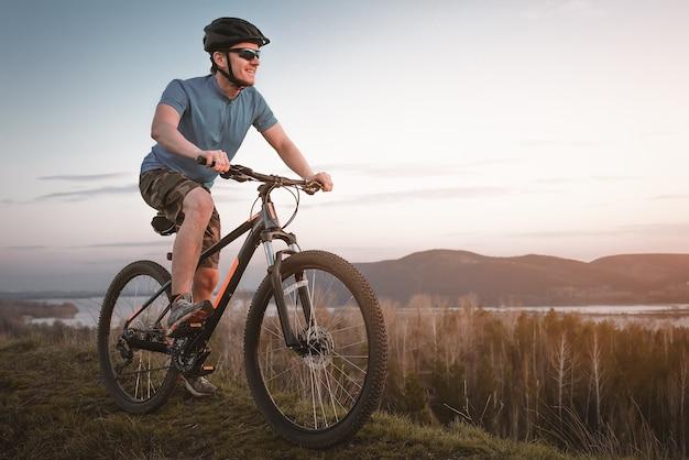Młody człowiek na rowerze górskim o zachodzie słońca.