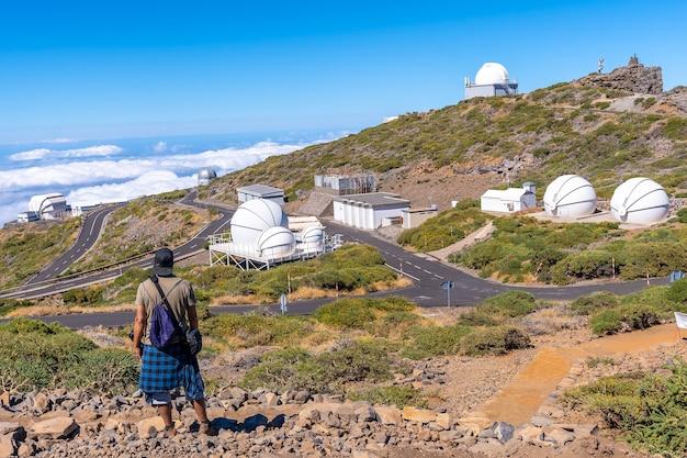 Młody człowiek na szlaku patrząc przez teleskopy parku narodowego roque de los muchachos na szczycie caldera de taburiente, la palma, wyspy kanaryjskie. hiszpania