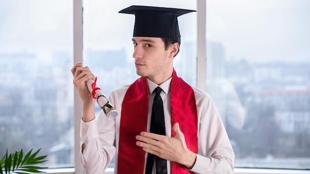 Młody człowiek na ukończeniu uniwersytetu online w domu z przewijaniem w rękach