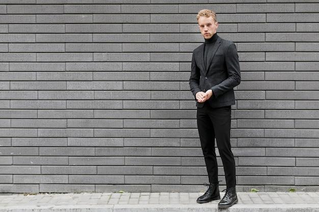 Młody człowiek na ulicy w pobliżu szarej ściany