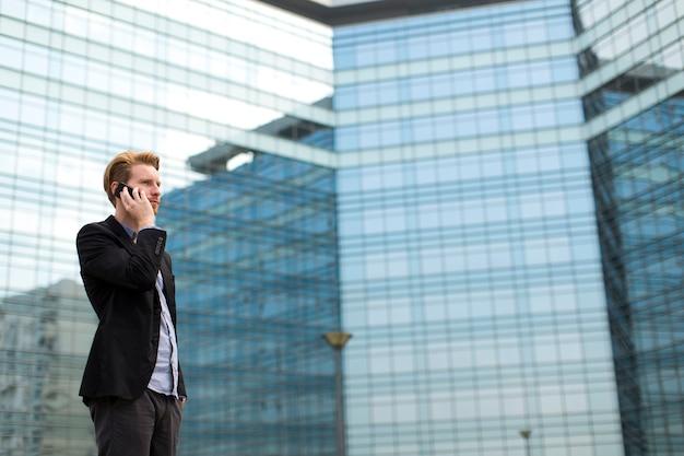 Młody człowiek na ulicy z telefonem komórkowym
