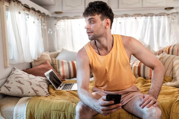 Młody człowiek na wakacjach z kamperem. podróżowanie z autokarawaną. koncepcja o podróżach i stylu życia na wakacjach